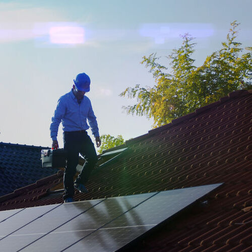 An Inspector Checks a Roof With Solar Panels.