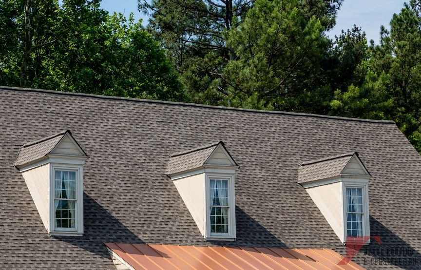 Three white wood dormers on an old grey shingle roof