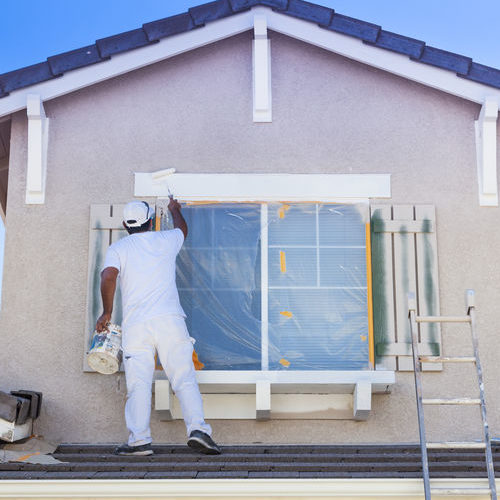 A House Painter Painting a House.