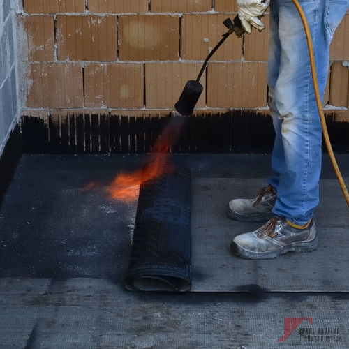 Contractor Installing Modified Bitumen Roofing